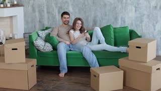 Happy Couple Watching tv Lying on the Couch, Moving Boxes