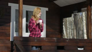 happy girl drinks tea on the terrace of a wooden house