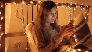 Happy Girl With Phone on a Bed Decorated With a Garland in the Evening