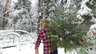 happy man walking with a Christmas tree in the winter forest