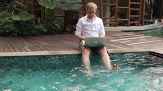 happy man working behind laptop sitting by the pool