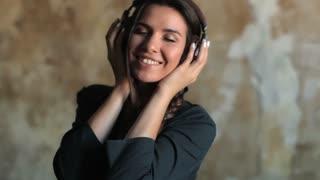 happy woman dances to music on headphones