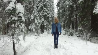 happy woman jumping in the winter forest