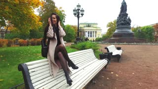 happy woman sitting on a bench in the autumn park