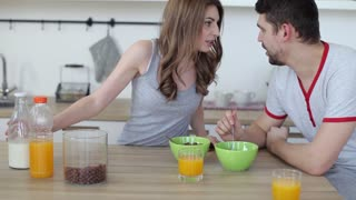 Happy Young Couple Eating Cereal With Milk in the Kitchen