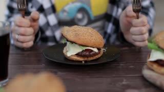 hungry man and a hamburger. men's hands hold a juicy burger