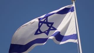 Israeli flag is developing against the blue sky