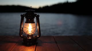 light from a kerosene lamp standing on a pier by the lake