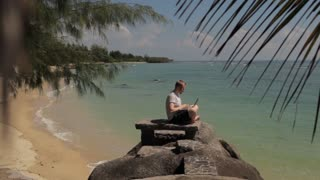male working on laptop on tropical beach