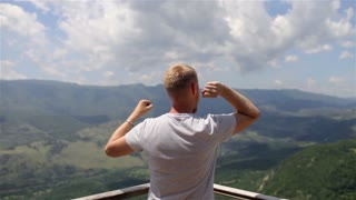 man celebrates the achievement with a view of the mountains