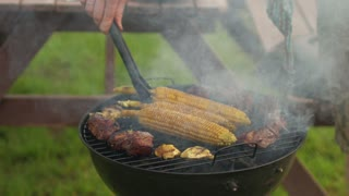 man cooking corn on the grill