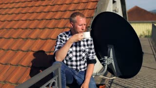 man drinking coffee sitting on the roof