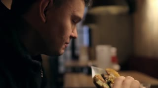 Man Eating a Big Burger With Sauce in a Bar