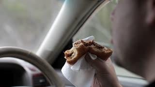 Man Eating a Burger at the Wheel of a Car