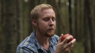 man eating an apple in the forest