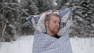 Man in a Blanket and With a Pillow Sleeping in the Winter Forest