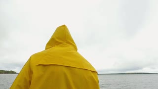 man in a yellow raincoat goes to a stone dock