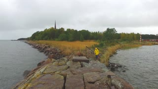man in a yellow raincoat goes to a stone pier