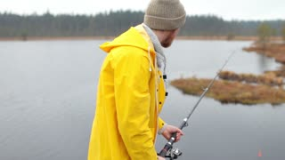 man in a yellow raincoat is fishing on the lake