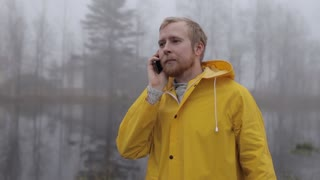 man in a yellow raincoat talking on the phone by the lake in a fog