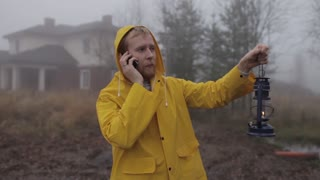 man in a yellow raincoat talking on the phone with a lantern by the lake in a fog