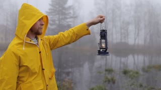 man in a yellow raincoat with a lantern by the lake in a fog