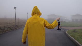 man in yellow raincoat with a kerosene lamp standing with his back by foggy street