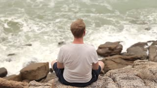 man is resting on the rocks on the seashore