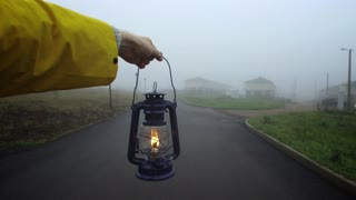 man lights the way with a lantern in the fog, A man's hand holds a kerosene lantern in the fog
