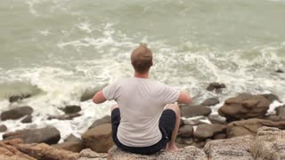 man pulls his hands up is resting on the rocks on the seashore