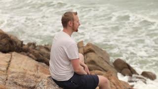 man resting on the rocky seashore