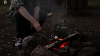 Man Roasting Marshmallow Over Campfire