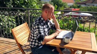 man talking on the phone, working with laptop on the summer terrace