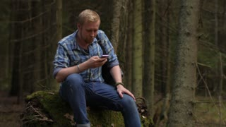 man traveler with a smartphone in the forest