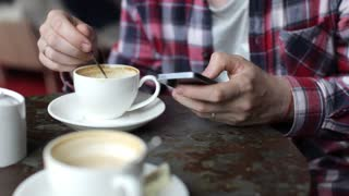 Man Using Mobile Phone in Coffee House. Close-Up