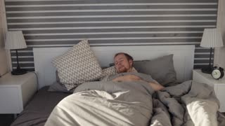 man wakes up from the alarm clock and tries to turn it off