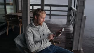 man with a tablet sits on the terrace of a house on the lake
