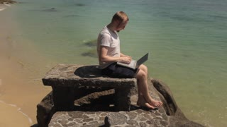 man working on laptop on tropical beach
