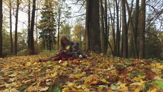 mommy with daughter sitting in autumn park