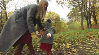 mother and daughter collect autumn leaves in the park