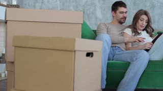 Moving a Young Couple, Sitting on the Couch Among the Boxes, Checking the List of Things