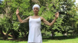 Pretty Girl is Doing Yoga in Park. Girl in White Doing Asanas on Nature
