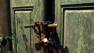 rusty chain with a lock on an old shabby green door