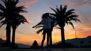 silhouette of a cheerful girl walking on the waterfront with palm trees at sunset