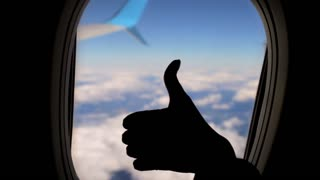 silhouette of a female hand a thumbs up, shows a class, against a background of clouds in an airplane window