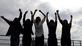 Silhouette of a Group of People Raising Their Hands up Victory Over a Sky Background