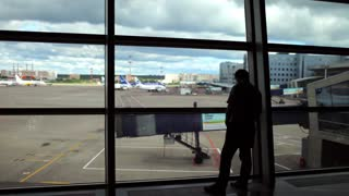 silhouette of a man at the airport waiting room window
