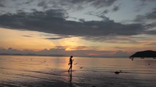 silhouette of a woman walking on the water on the beach at sunset