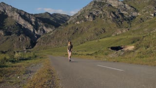 slender girl on a Kick scooter on a flat road among the mountains
