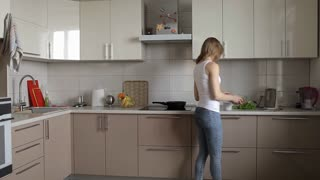 Slender Girl Prepares Food, Salad in the Kitchen